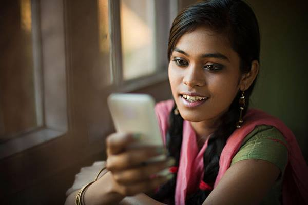 Indian woman reading information on smart phone