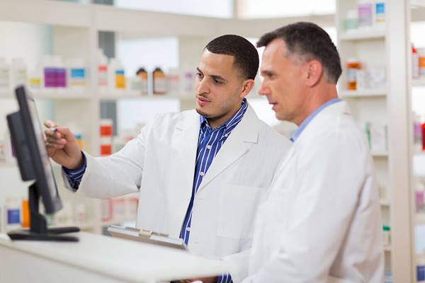 two pharmacists looking at computer