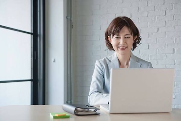 professional woman using laptop and smiling
